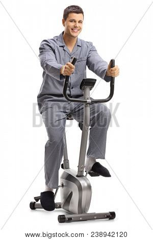 Young guy in pajamas exercising on a stationary bike isolated on white background poster