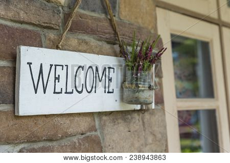 White Wood Welcome Sign  On Brick Wall With Grass Pot Of Small Flower. Close Up Wood Welcome Sign In