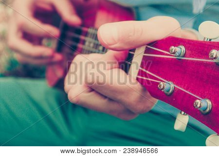 Photo Depicts Musical Instrument Ukulele Guitar In The Hands Of Player. Musician Fingers Are Playing