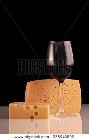 One Glass Bocal Of Red Wine Standing With Two Kinds Of Fresh Tasty Cheese Reflecting On White Table