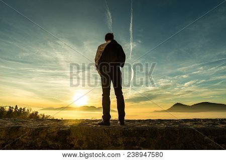 Businessman In A Suit Standing Outdoors Silhouetted Against A Colorful Sunrise With The Fiery Sun Pe