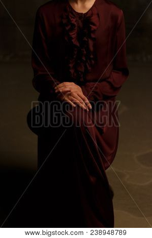 a girl in a vintage, plum dress is sitting on a chair. modesty. purity. basement. dungeon. crossed arms on knees. poster