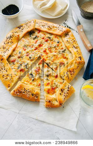 Arabic And Middle Eastern Food Concept. Cheese And Labneh Savory Galette With Olives On A Baking Pap