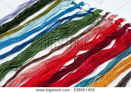 Bright Multicolored Embroidery Thread Yarns. Skeins Of Multicolored Embroidery Threads On Dark Felt