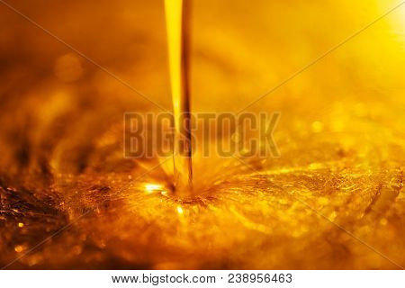 Orange Liquid And Viscous Stream Of Motorcycle Motor Oil Like A Flow Of Honey Close-up