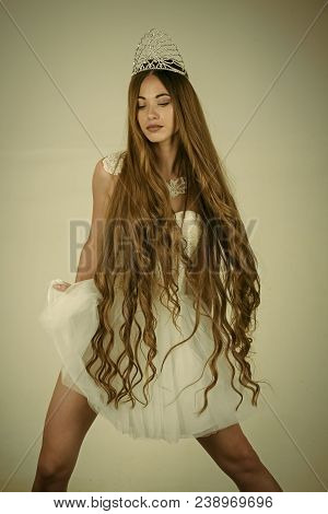 Beauty Salon And Wedding Fashion. Woman With Long Hair White Dress And Crown. Haircare And Prom Quee