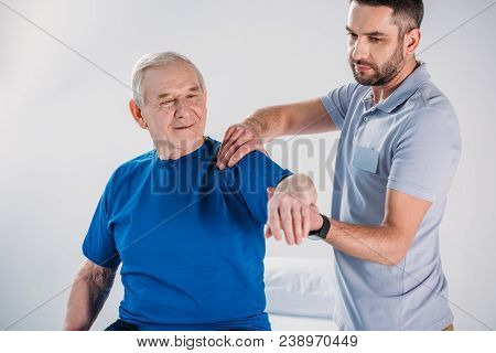 Portrait Of Physiotherapist Doing Massage To Smiling Senior Man On Massage Table