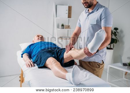 Partial View Of Physiotherapist Massaging Senior Mans Leg On Massage Table