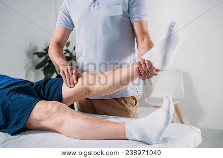 Cropped Shot Of Physiotherapist Massaging Senior Mans Leg On Massage Table