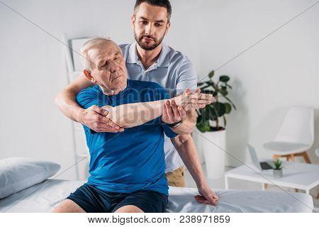 Portrait Of Physiotherapist Doing Massage To Senior Man On Massage Table
