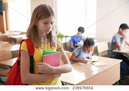 Sad teenage girl in classroom. Bullying at school