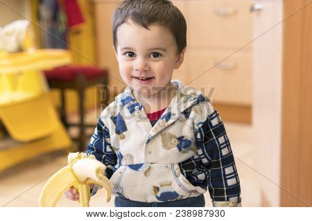Funny Boy 2 Years Old Eating Banana. Happy Baby Boy Holding Two Hands Of Bananas.