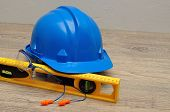 A hardhat, level, safety spectacles and earplugs poster
