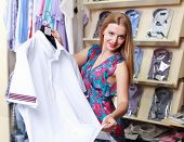 Young beautiful girl in a clothing store salesman poster