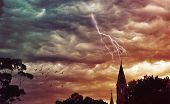Atmospheric grunge textured stormy sky and lightning over a church.  poster