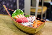 Set of sashimi in wooden ship bowl consist of Toro, salmon (sake), octopus (tako), tuna (maguro) and imitation crab stick put on ice - Japanese food concept. poster