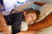 Little preschool kid boy sleeping in bed with colorful lamp. School child dreaming and holding plush toy. Kid angry of darkness. poster