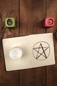 An overhead photo of an open grimoire with candles. Wicca ritual objects, shot from above on a dark background with a place for text poster