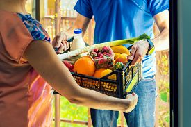 Woman Accepting Groceries Box From Delivery Man At Home