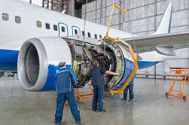 Assembling, Replacing Engine Parts Of The Plane After Repair. Specialist Mechanic Controls The Crane