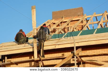 Roofing Contractors Installing House Framework, Roof Board For Asphalt Shingles. Roofing Contractor.