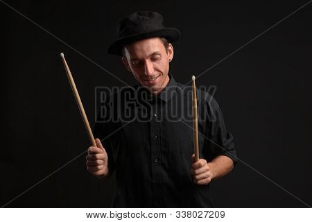 Stylish Man Drummer In A Black Shirt And Hat Playing Drums With Sticks Over Dark Background. Jazz Mu
