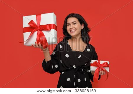 Smiling Brunette Woman In A Black Dress Choosing Between Small And Big Christmas Giftboxes With Red