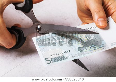 A Man Cuts Five Euros. Concept On The Topic Of Devaluation Of Money In The Country