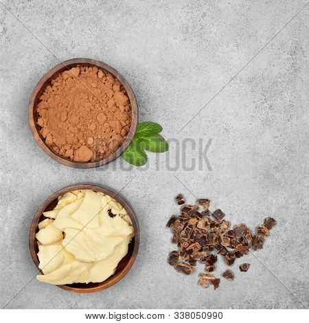 Cocoa Butter, Cocoa Powder, Mint And Carob On Gray Stone Background. Top View With Copy Space
