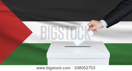 Election In Palestine. The Hand Of Man Putting His Vote In The Ballot Box. Waved Palestine Flag On B
