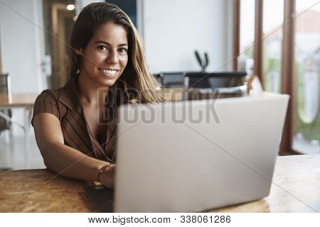 Attractive And Successful Hispanic Woman Smiling As Holding Hands Keyboard, Using Laptop, Look Camer