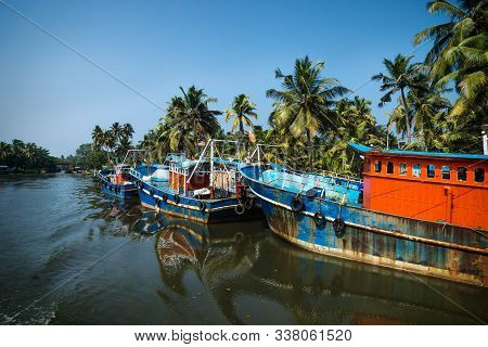 Row Of Ocean Fishing Boats From The Back Along The Canal Kerala Backwaters Shore With Palm Trees At