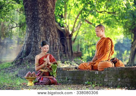 Thai Woman With Traditional Dress Sit Pray Respect Monk Under Big Tree In Forest , Present Buddhism