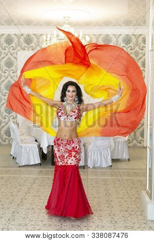 Oriental Dancer In A Red-yellow Dress. Belly Dancer Throws Ends Of Her Beautiful Orange Skirt Into T