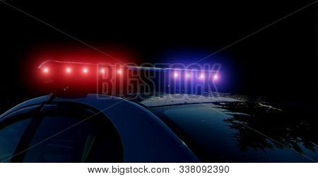 Police Patrol On The Street At Night. Flashing Red And Blue Police Car Lights In Night Time. Light A