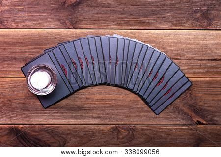 Fortune Telling Cards On A Wooden Table With A Burning Candle. Top View, Place For Text. Runic Cards