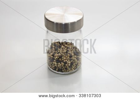 Three Colors Pepper In Glass Jar On White Table
