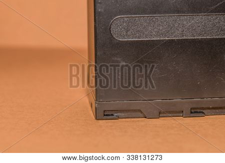 Closeup Side View Of Used Lithium-ion Battery On Brown Background. Selective Focus On Locking Guides