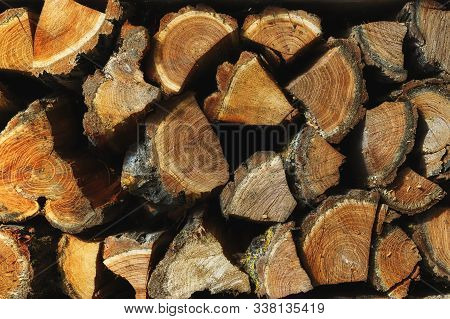 Background Of Firewood. The Texture Of Chopped Firewood On A Dark Background. A Bunch Of Firewood. H
