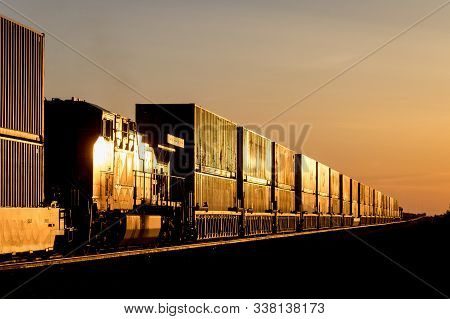 Locomotive And Train Carrying Shipping Containers In Golden Sunset On The Canadian Prairie
