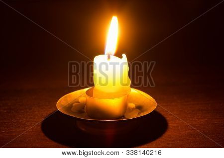 Burning Candle On A Wooden Table At Night