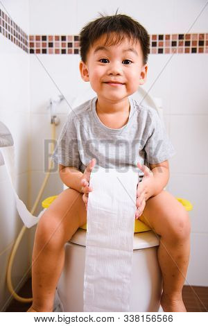Asian Little  Kid 2-3 Years Old Sitting On A Kid Bathroom Accessory Toilet And He Play Papers Toilet