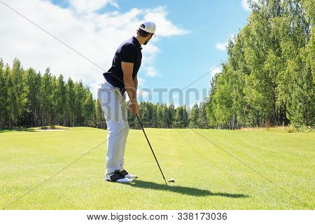 Full Length Of Golf Player Playing Golf On Sunny Day. Professional Male Golfer Taking Shot On Golf C