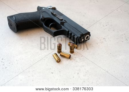 Bullets With Handgun In The Back Of The Scene With Focus On The Bullet