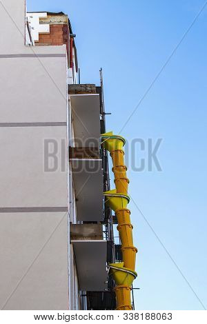 Suspended Sections Of Yellow Plastic Garbage Chute On A Facade Of Building Under Construction Agains