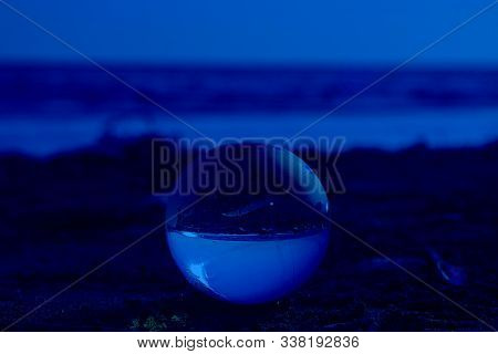 Glass Ball In Focus On The Beach Send Near The Sea With Upsidedown Reflection And Lighs Flecks On Th