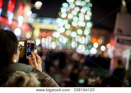 Strasbourg, France - Dec 20, 2016: Rear View Of Woman Taking Photograph With The Smartphone O The Bi