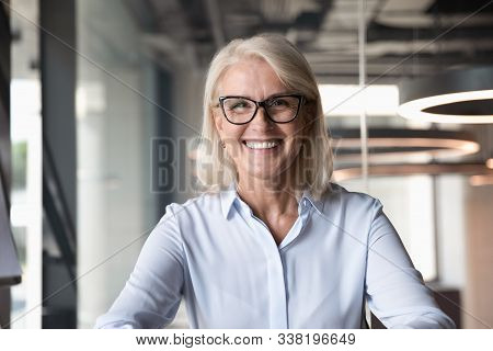 Headshot Of Middle-aged Businesswoman Posing At Workplace