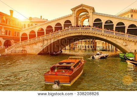 Rialto Bridge Over The Grand Canal At Sunset, Venice, Italy. It Is A Famous Landmark Of Venice. Boat
