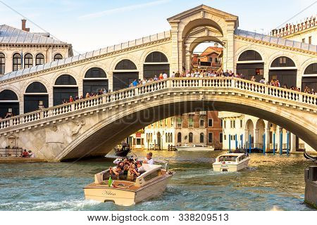 Venice, Italy - May 18, 2017: Water Taxi With Tourists Sails On Grand Canal Under The Rialto Bridge